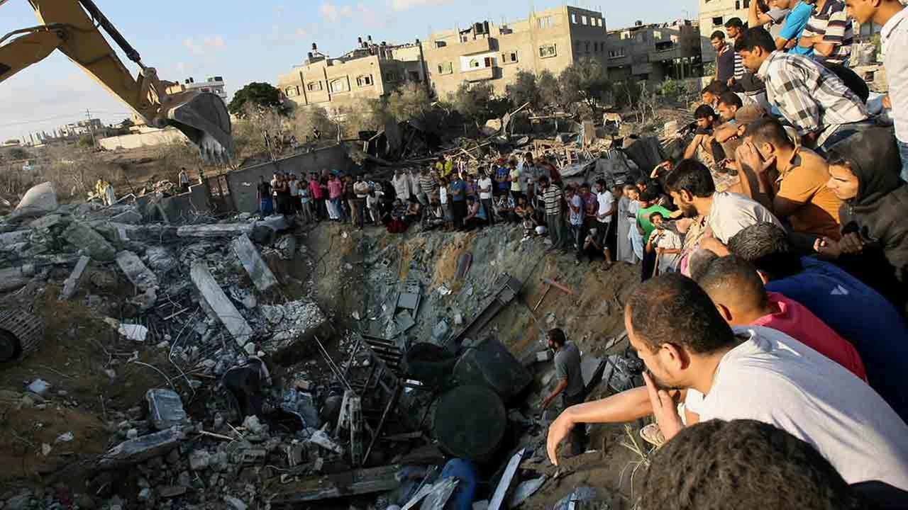 Palestinians gather around the rubble of a building where at least 20 members of the Al Najar extended family were killed by an Israeli strike in the southern Gaza Strip.