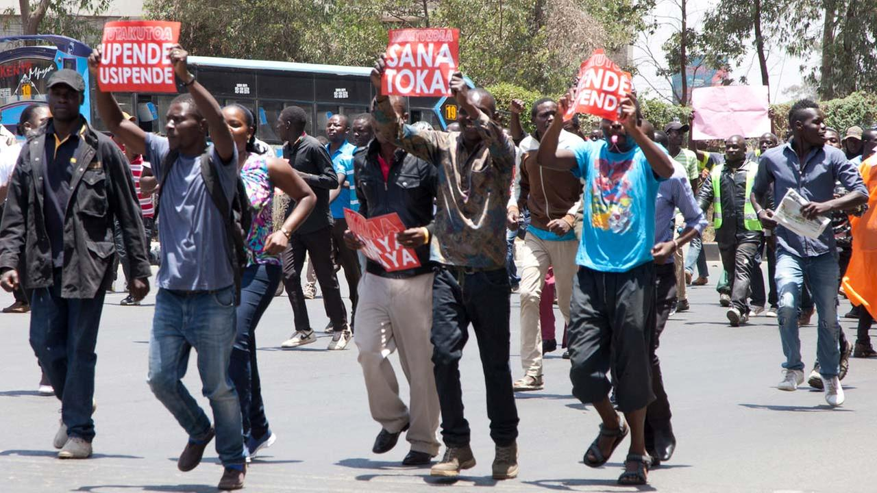 Opposition party supporters shout slogans as they hold posters which reads You like it or Not You have to Go and Uhuru Bees are coming as they march in Nairobi.