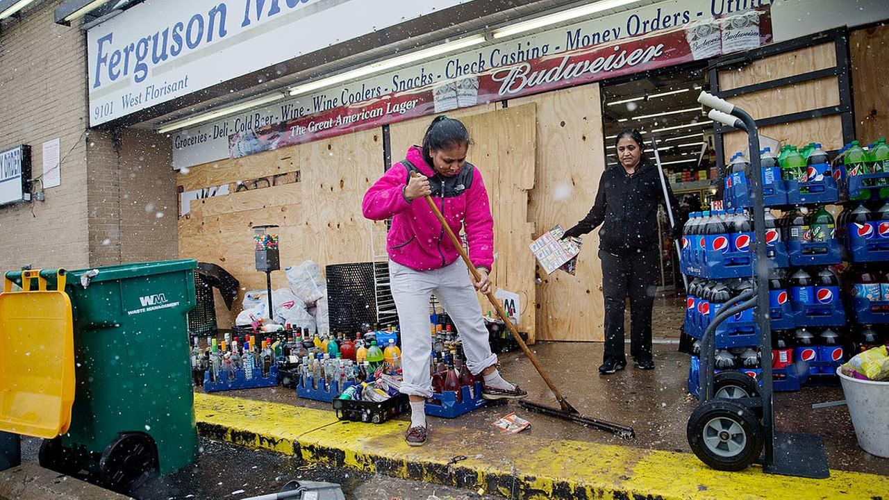 Anjana Patel cleans up the damage from Mondays riots at her store, Ferguson Market and Liquor, Wednesday, Nov. 26, 2014, in Ferguson, Mo.