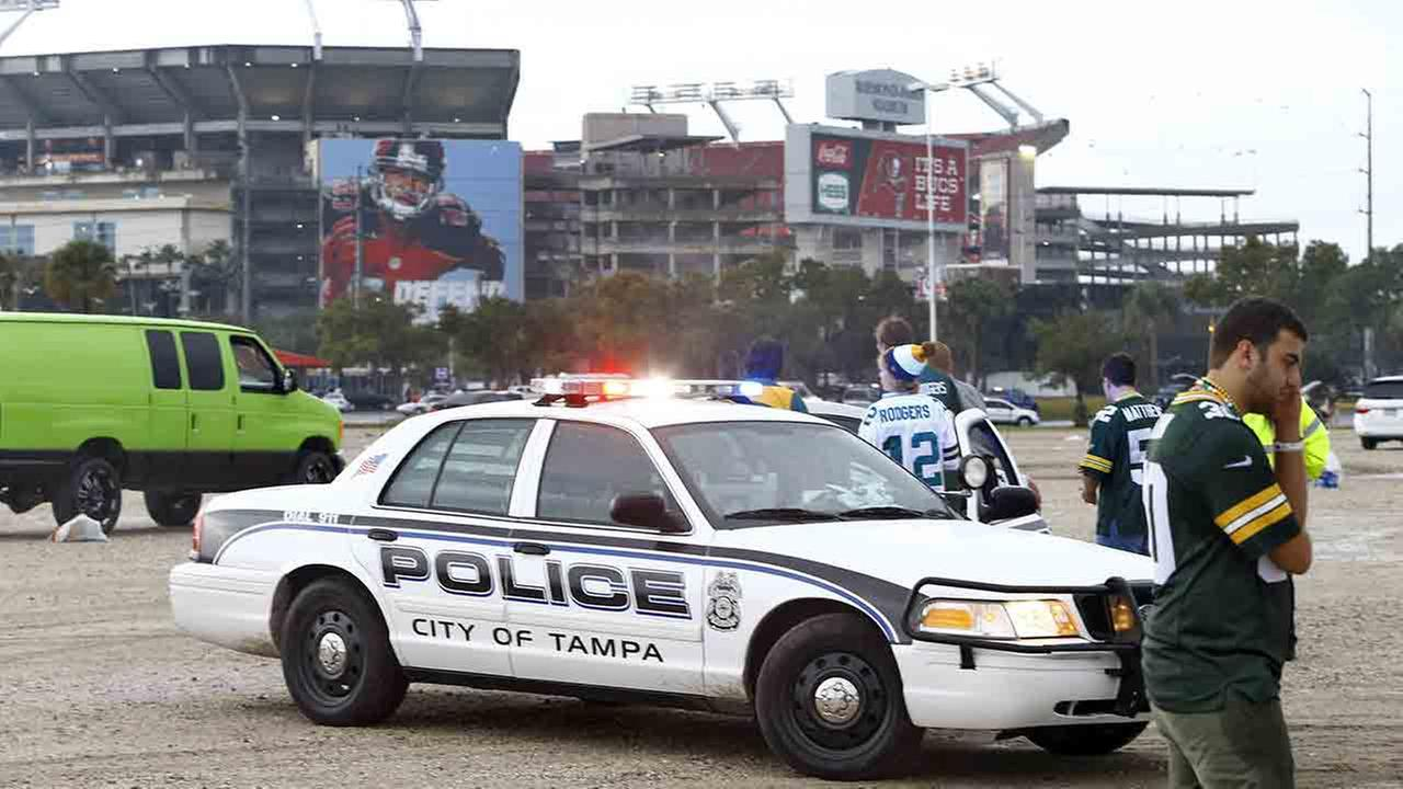 Tampa Police Officers talk to spectators after football fans were reportedly taken to the hospital with injuries after a lightning strike near the Raymond James Stadium.