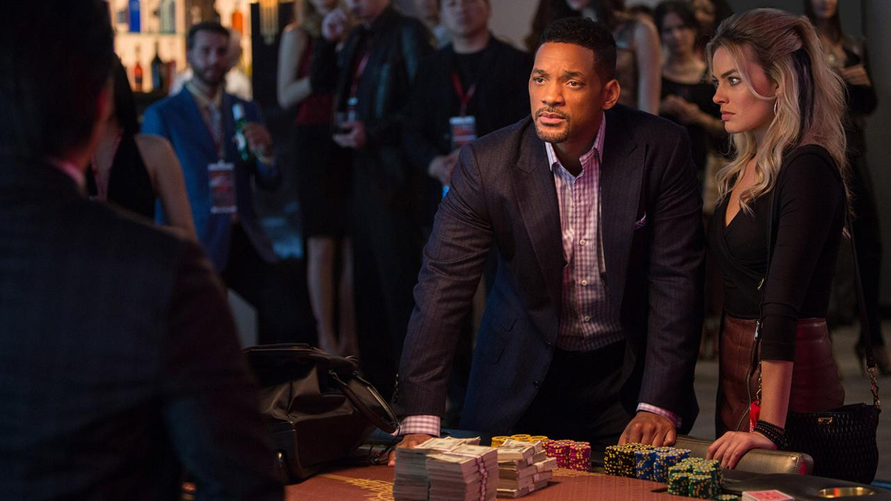 In this image released by Warner Bros. Pictures, Will Smith, center, and Margot Robbie, right, appear in a scene from the film, Focus.