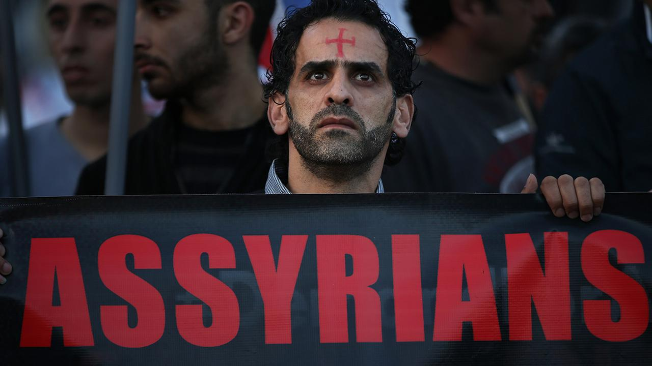 An Assyrian man with a red cross painted on his forehead walks during a protest of several hundred people in solidarity with Christians abducted in Syria and Iraq, Feb. 28, 2015.