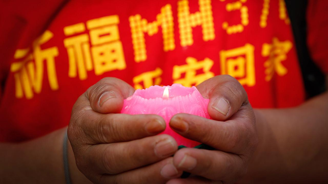 An unidentified Chinese family member of a passenger on board the missing Malaysia Airlines Flight 370 holds a Lotus candle as they pray at a temple in Kuala Lumpur, Malaysia, Sunday, March 1, 2015.