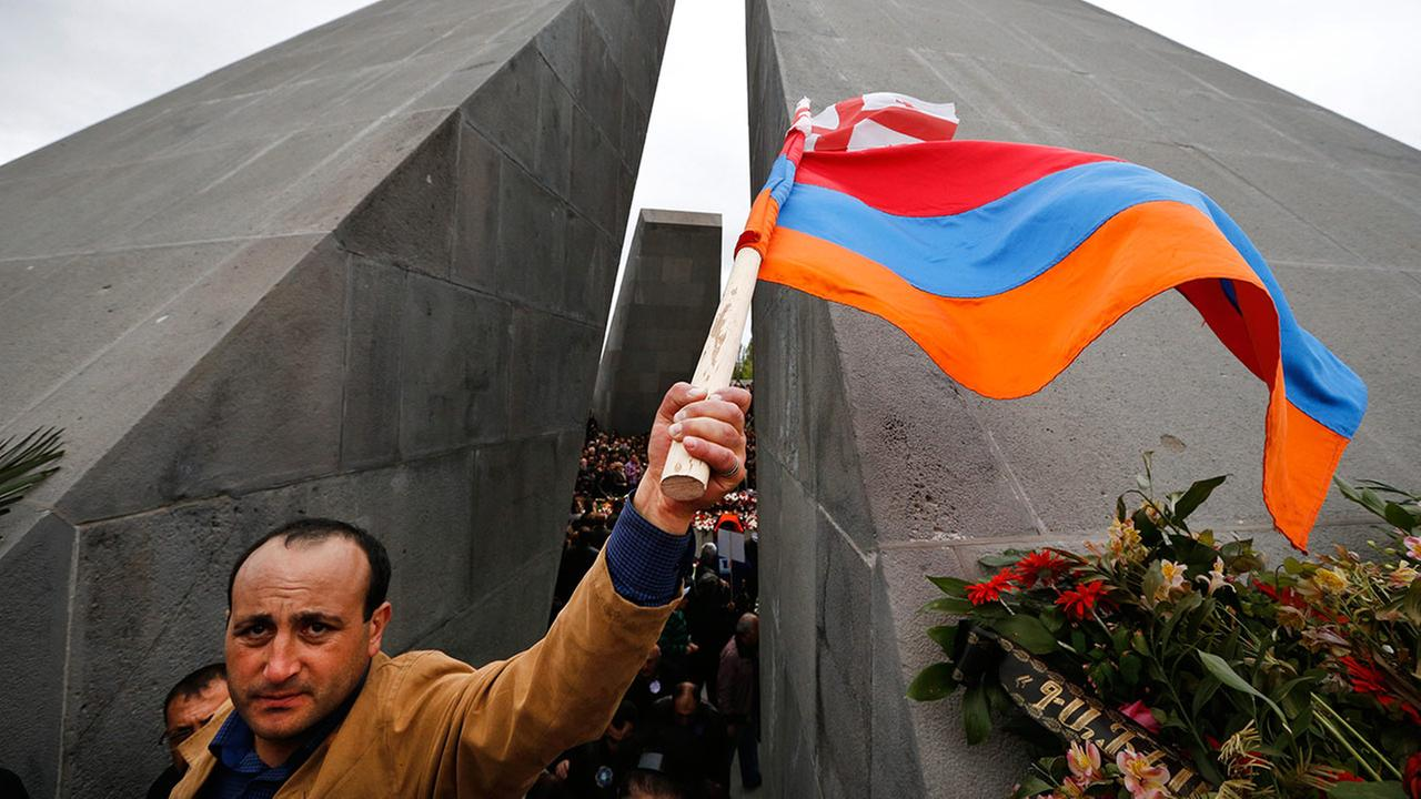A man waves Armenian and Georgian flags at a memorial to Armenians killed by the Ottoman Turks, during marking the centenary of the mass killings, in Yerevan, Armenia, Friday, April 24, 2015.