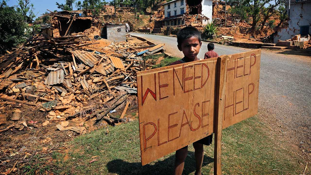 A Nepalese boy stands outside his village with a signboard asking for help in Pauwathok village, Sindhupalchok district, Nepal, Saturday, May 2, 2015.