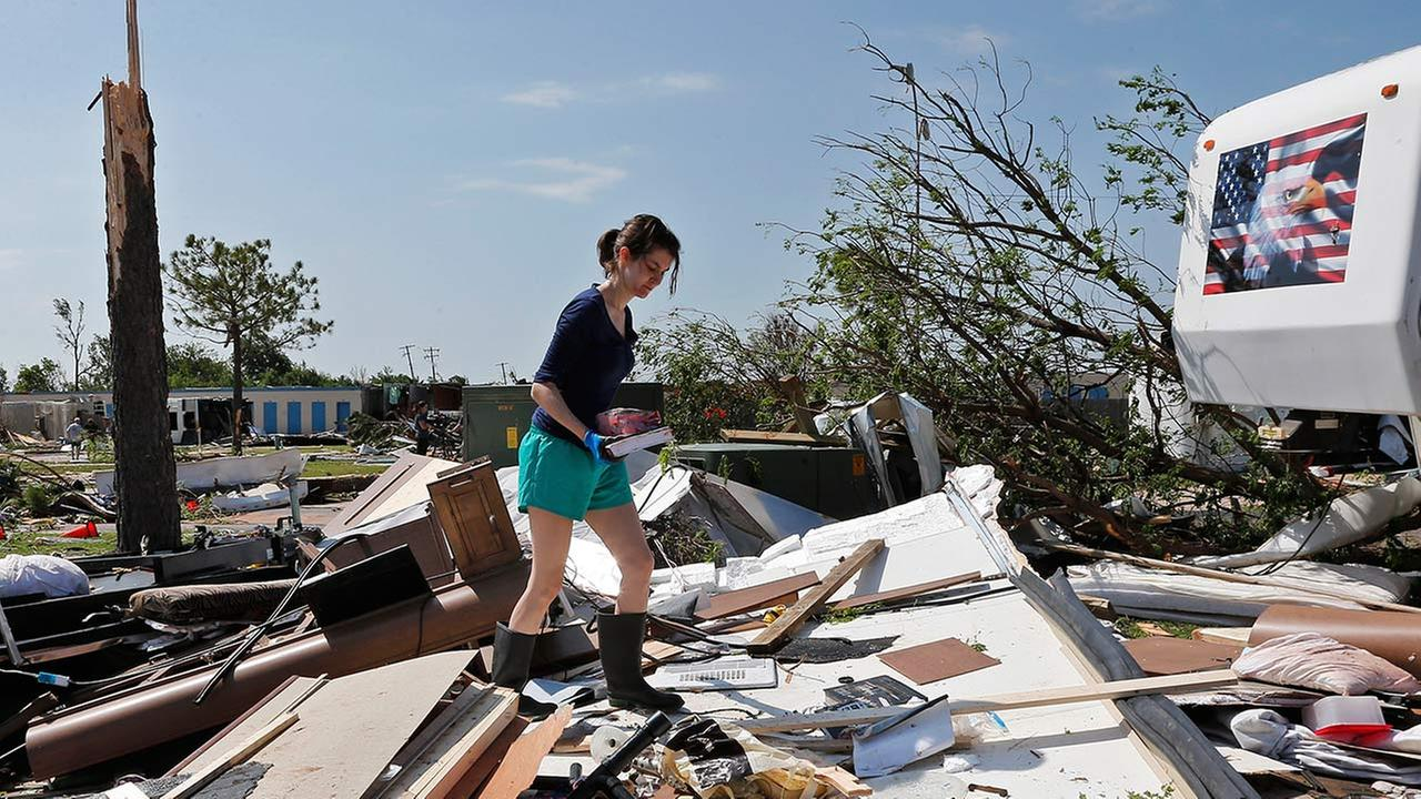 In this Thursday, May 7, 2015 photo, Dillan Taylor salvages items from her destroyed recreational vehicle in Oklahoma City.