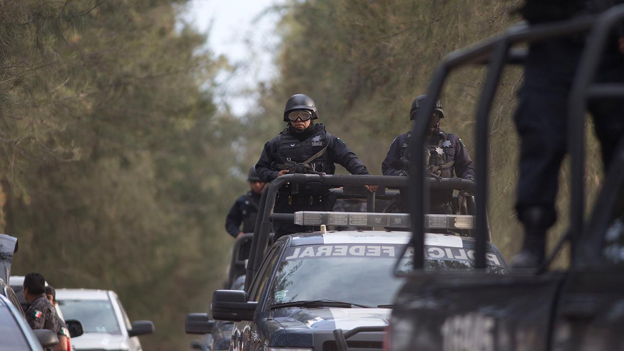 Mexican Federal Police stand guard near the entrance of Rancho del Sol, near Ecuanduero, in western Mexico, Friday, May 22, 2015.