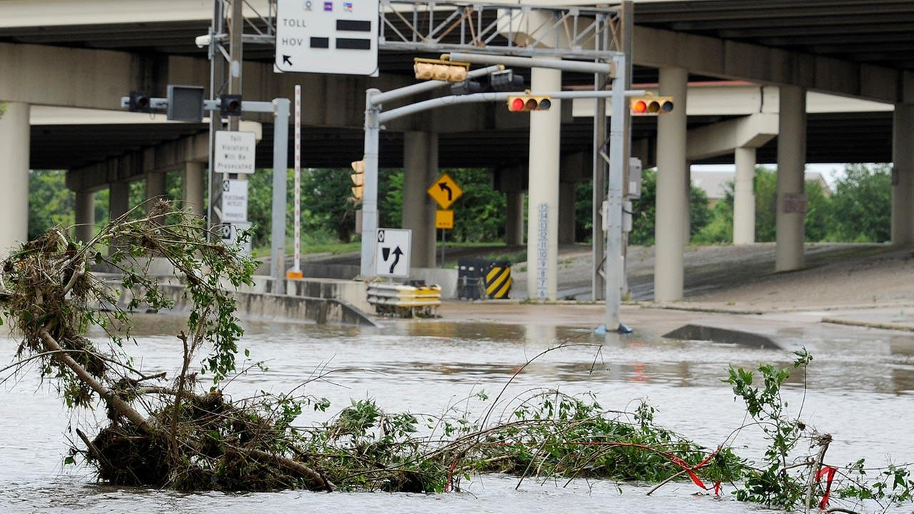 A highway entrance is covered in water and debris after flood waters overran the banks of the bayou in downtown Houston, Tuesday, May 26, 2015.