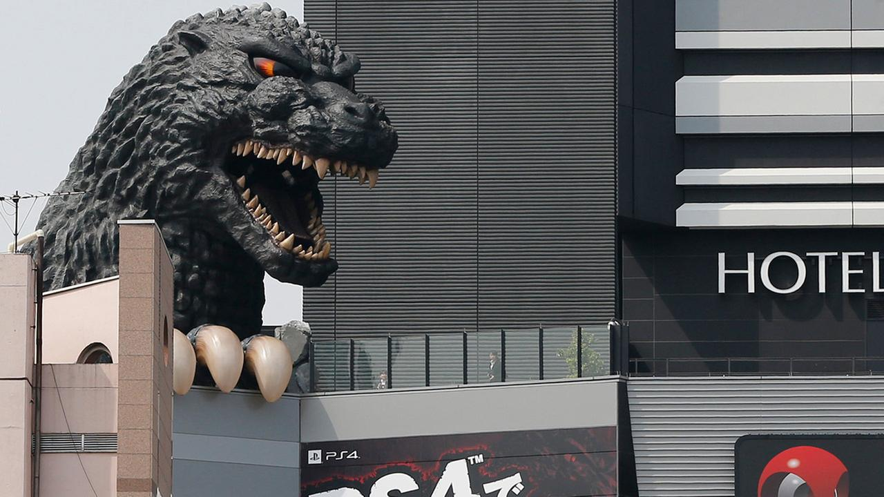 In this May 28, 2015 photo, Godzillas head dwarfs visitors with an advertisement for its first video game of Sony PlayStation 4 home machine in Tokyo.