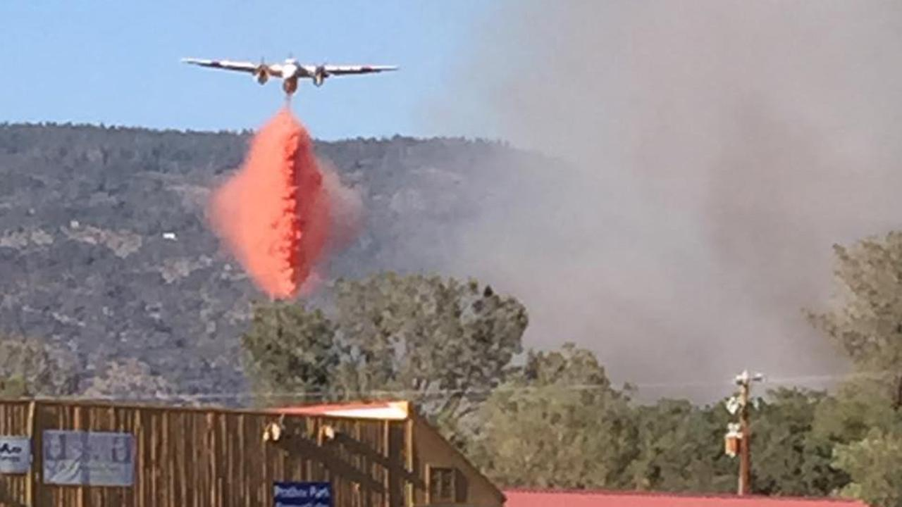An air tanker drops retardant on a fire in the community of Prather on Sunday, June 14, 2015.