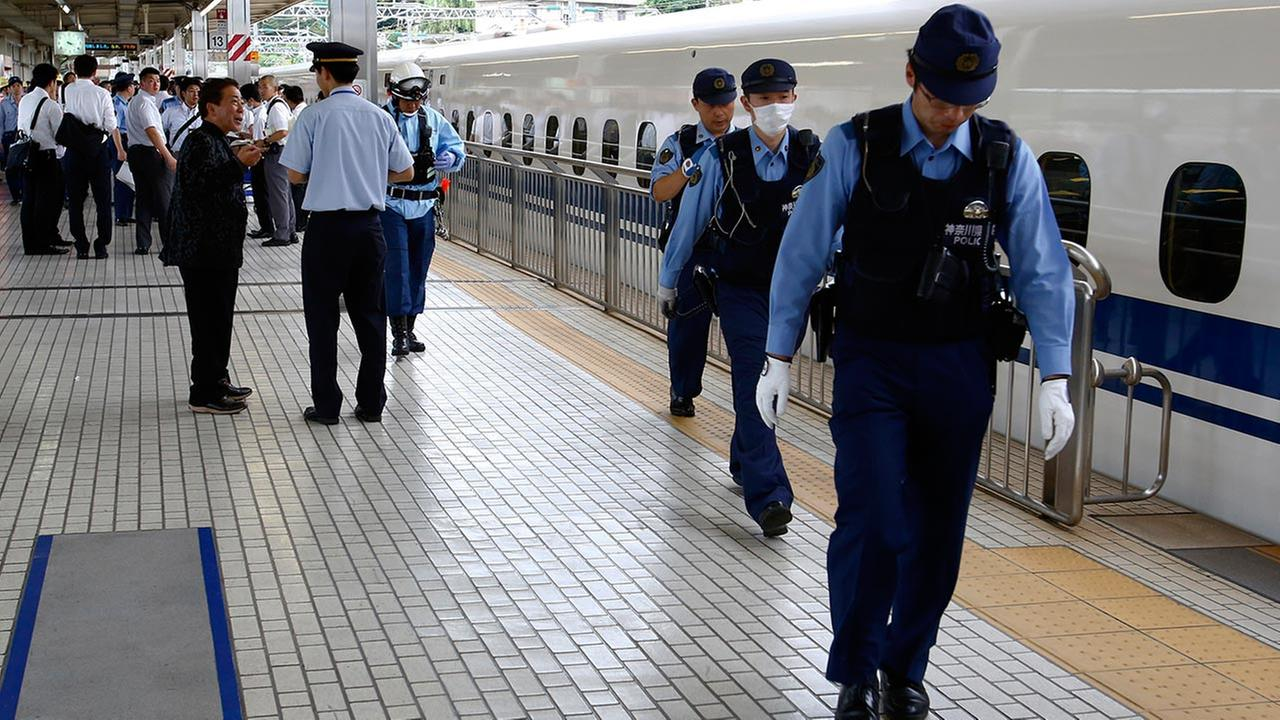 A passenger, left, talks with a station employee on a platform after getting off a high-speed bullet train where a man set himself of fire, at Odawara station in Odawara, west of Tokyo, Tuesday, June 30, 2015.