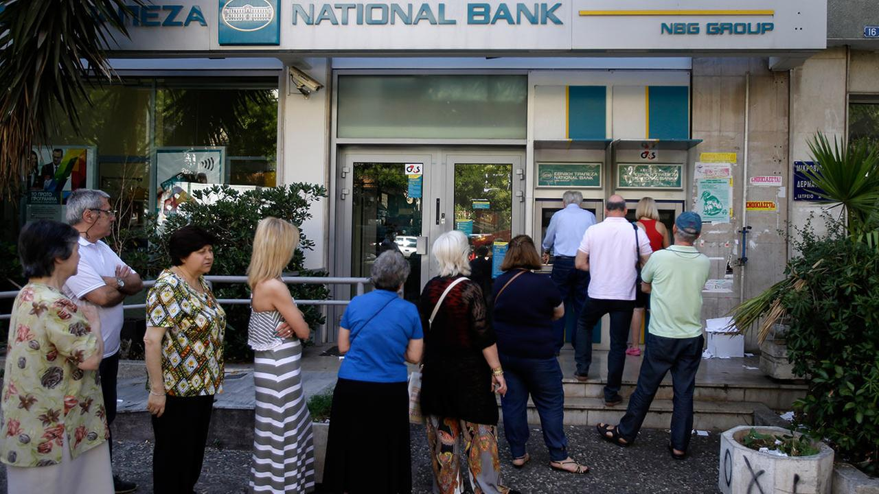 People stand in a queue to use an ATM outside a closed bank, next to a sign on the plant, bottom right, reading NO in Athens, Tuesday, June 30, 2015.