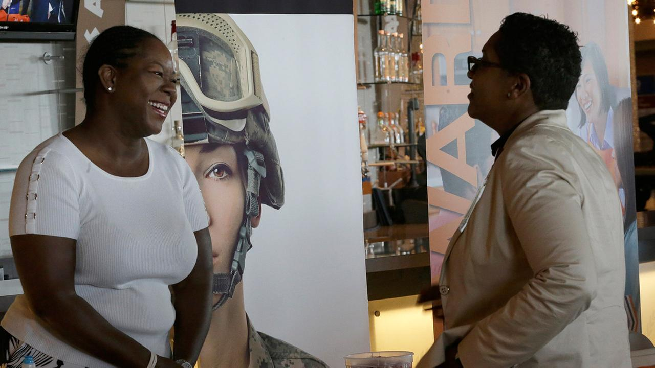 In this photo taken Tuesday, June 30, 2015, Sophia Lewis, left, with PSEG Long Island, speaks to an attendee about employment opportunities during a job fair at Citi Field in New York.