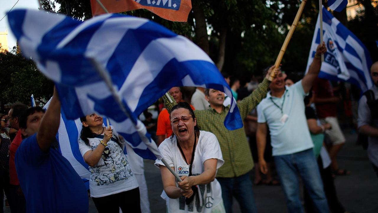 A supporter of the No vote waves a Greek flag after the referendums exit polls at Syntagma square in Athens, Sunday, July 5, 2015.