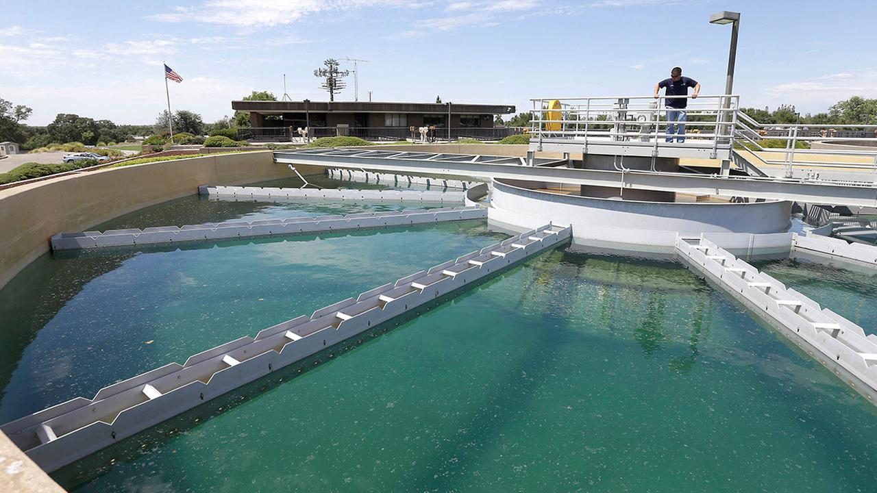 In this photo taken Thursday, July 2, 2015, Dan Johnson, a treatment plant operator inspects a sediment pond at the Roseville Water Treatment Plant in Granite Bay, Calif.