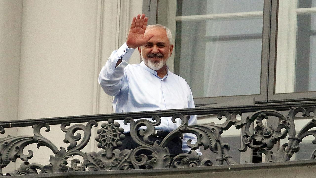 Iranian Foreign Minister Mohammad Javad Zarif waves to journalists from a balcony of the Palais Coburg where closed-door nuclear talks with Iran continue in Vienna, Austria, Monday, July 13, 2015