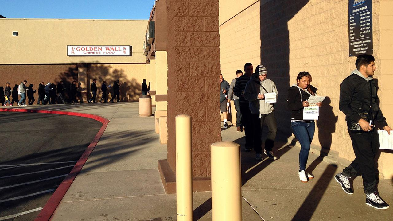 FILE - In this Jan. 23, 2015, file photo, immigrants stand in a long line to enter into the California Department of Motor Vehicles office in the Granada Hills area of Los Angeles.