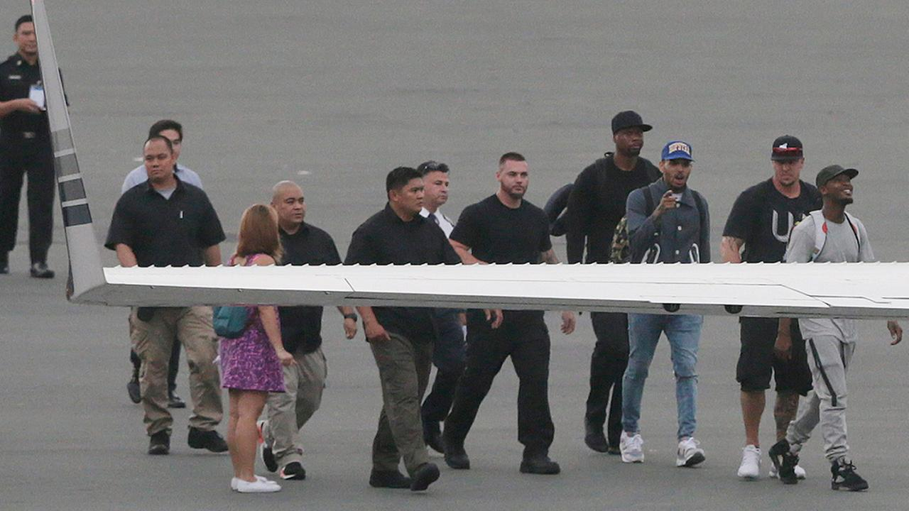 Grammy award-winning singer Chris Brown, third from right, walks to board a chartered jet at the old Manila Domestic Airport in suburban Pasay city, south of Manila, Philippines, Friday, July 24, 2015.