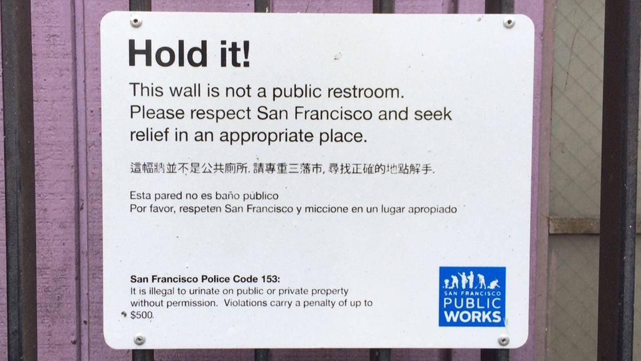 A sign reading Hold it! This wall is not a public restroom. Please respect San Francisco and seek relief in an appropriate place, hangs above a wall in San Francisco.