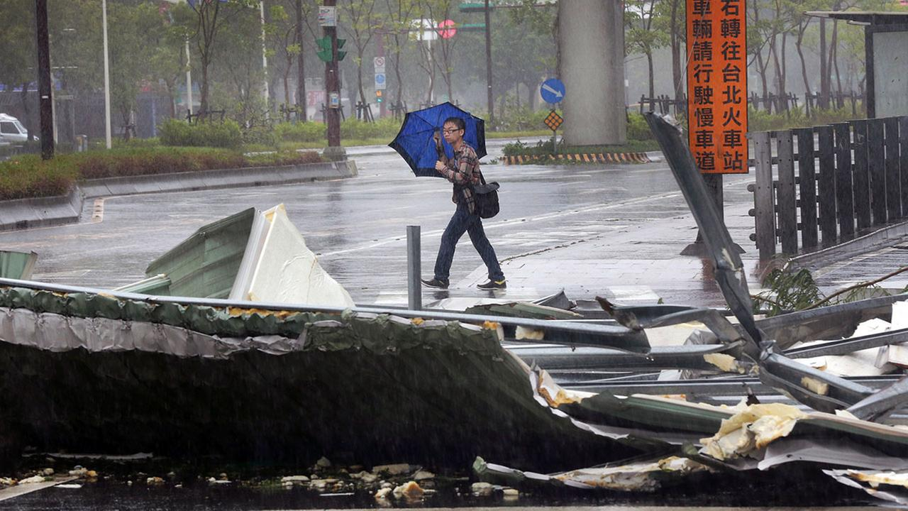 A man carrying an umbrella passes a mangled rooftop brought down by strong winds from Typhoon Soudelor in Taipei, Taiwan, Saturday, Aug. 8, 2015.