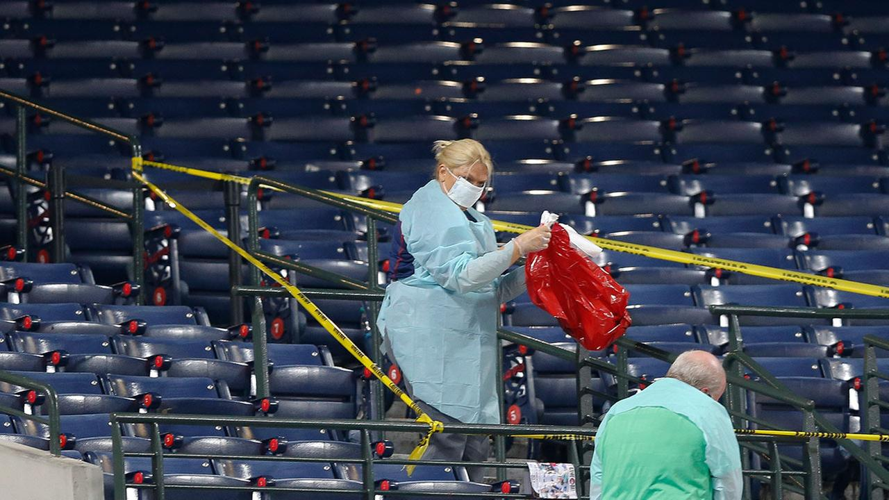 People clean a section of the lower seating area at Turner Field where a fan fell from the upper deck during a baseball game between the Atlanta Braves and the New York Yankees, Saturday, Aug. 29, 2015, in Atlanta.
