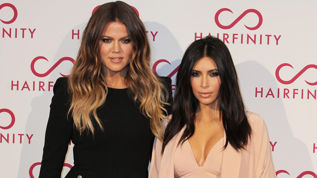 Kim and Khloe Kardashian, left, pose for photographers on her arrival at the Hairfinity party in central London, Saturday, Nov. 8, 2014.