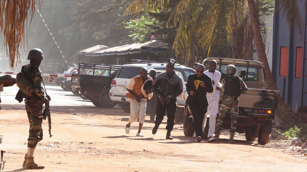 People run to flee from the Radisson Blu Hotel in Bamako, Mali, Friday, Nov. 20, 2015. (AP Photo/Harouna Traore)