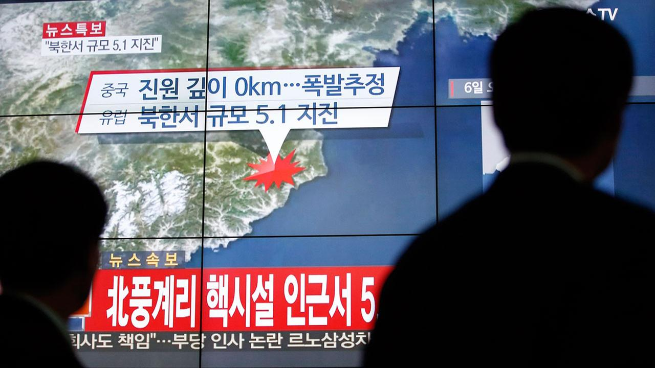 People walk by a screen showing the news reporting about an earthquake near North Koreas nuclear facility, in Seoul, South Korea, Wednesday, Jan. 6, 2016. (AP Photo/Lee Jin-man)