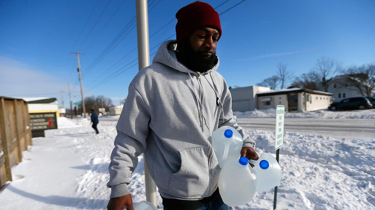 Lemott Thomas carries free water being distributed at the Lincoln Park United Methodist Church in Flint, Mich. A GM plant stopped using the water, saying it was rusting its parts.