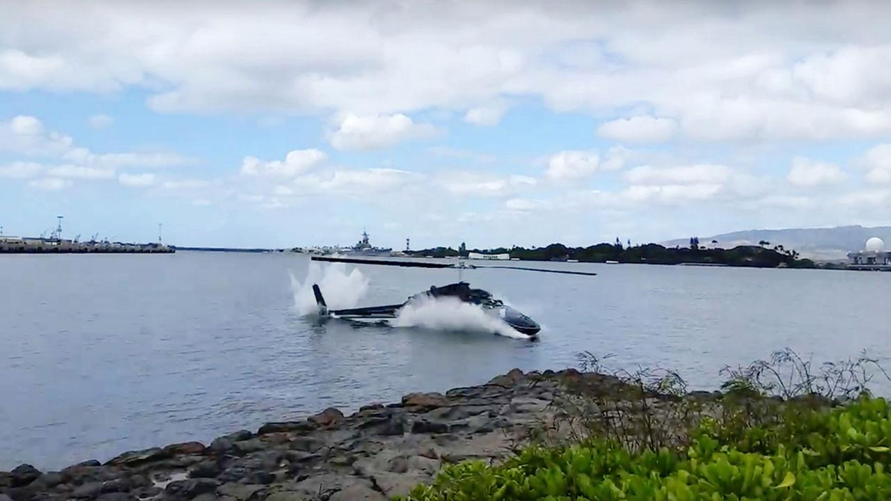 In this image taken from video provided by Shawn Winrich, a helicopter crashes near Parl Harbor, Hawaii on Thursday, Feb. 18, 2016.  (Shawn Winrich via the AP)
