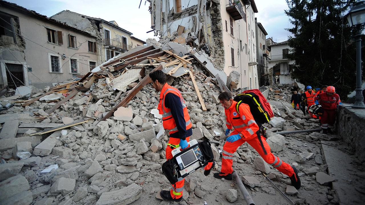 Rescuers search a crumbled building in Arcuata del Tronto, central Italy, where a 6.1 earthquake struck just after 3:30 a.m., Wednesday, Aug. 24, 2016. (AP Photo/Sandro Perozzi)
