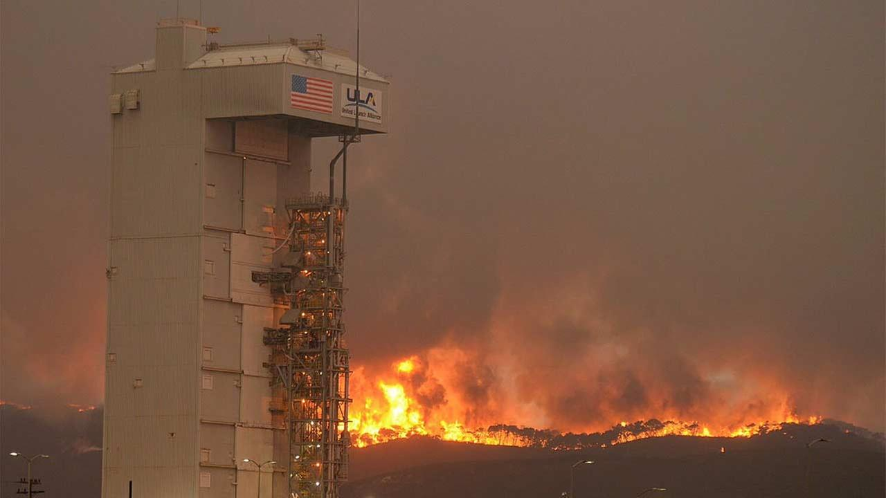 The CanyonFire continues to burn on VAFB. In the foreground is Space Launch Complex-3 housing the Atlas V rocket and WorldView 4 satellite.