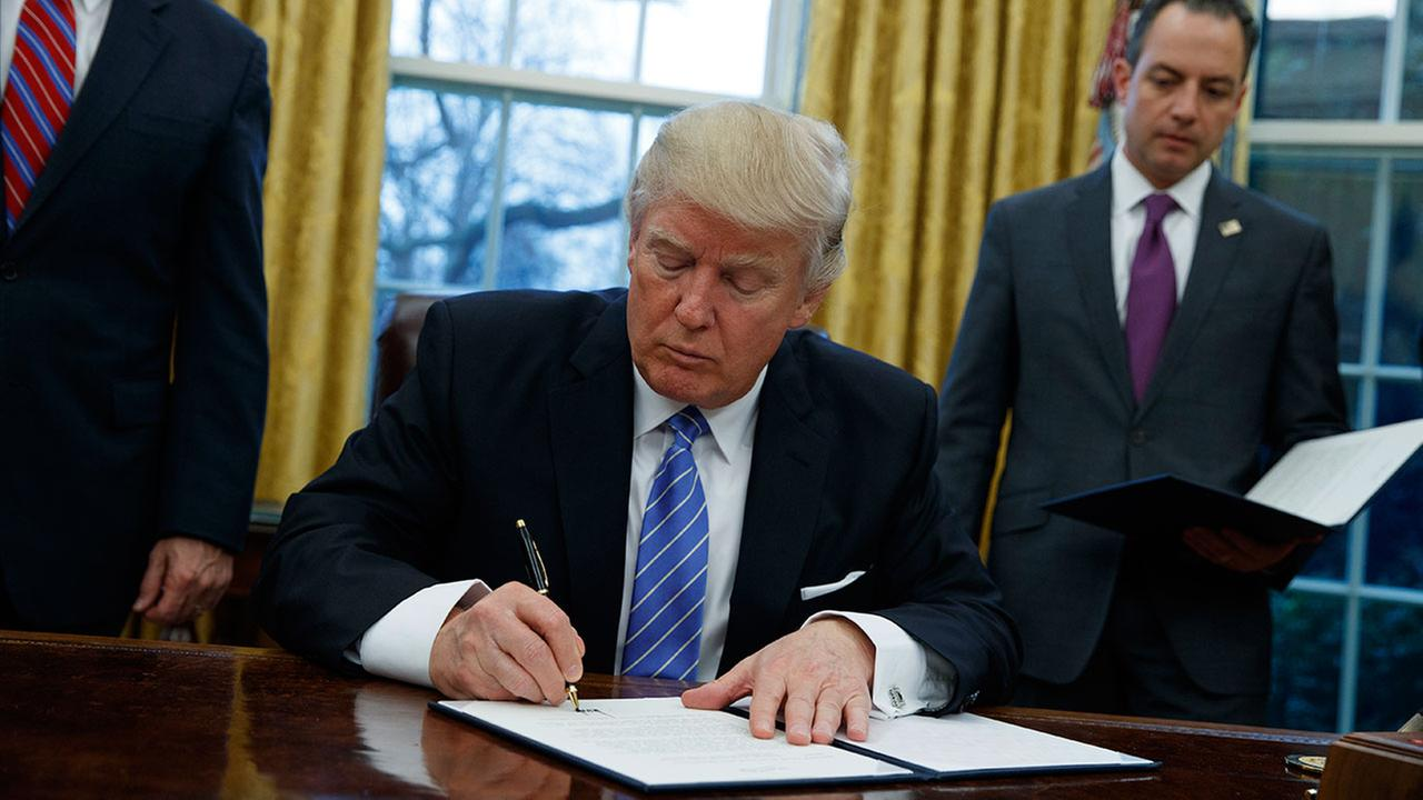 President Donald Trump signs executive order to withdraw U.S. from the 12-nation Trans-Pacific Partnership trade pact (AP Photo/Evan Vucci)