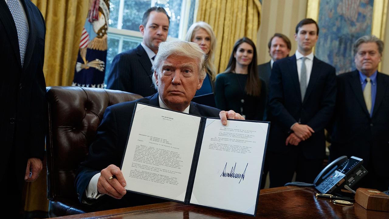President Donald Trump shows his signature on an executive order on the Keystone XL pipeline, Tuesday, Jan. 24, 2017 (AP Photo/Evan Vucci)
