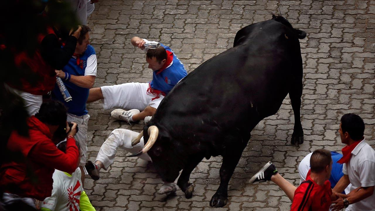 U.S. runner Bill Hillmann, 35, from Chicago is gored on his right leg by a Victoriano del Rio ranch fighting bull during the running of the bulls