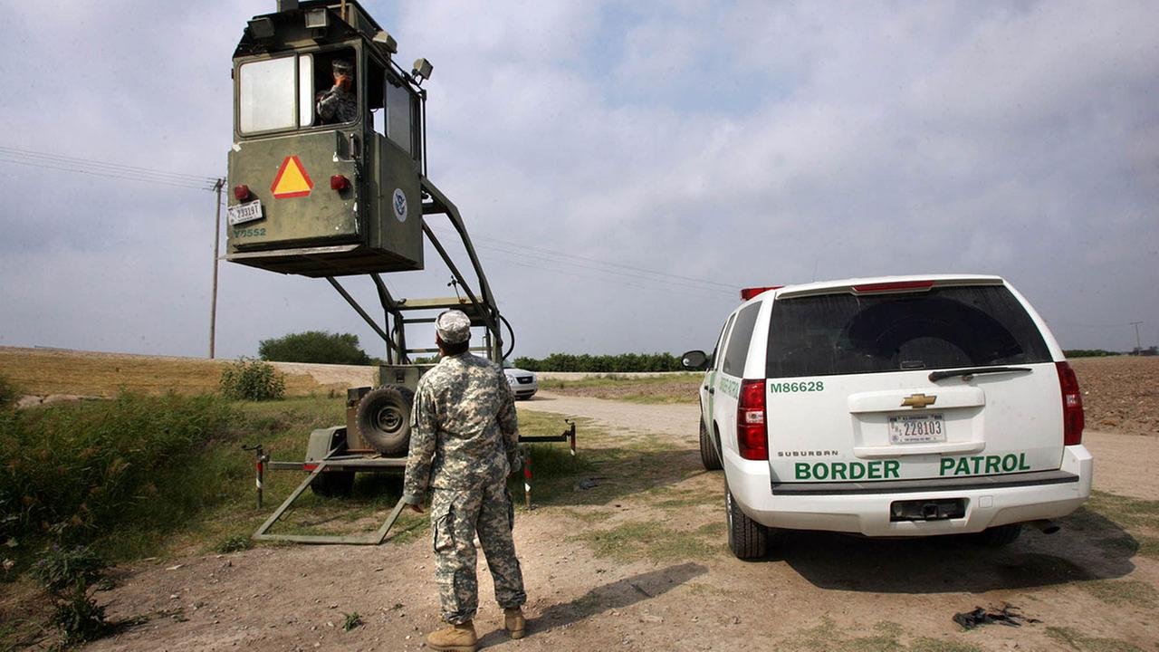FILE - In this April 19, 2011, file photo, a member of the National Guard checks on his colleague inside a Border Patrol Skybox near the Hidalgo International Bridge in Texas