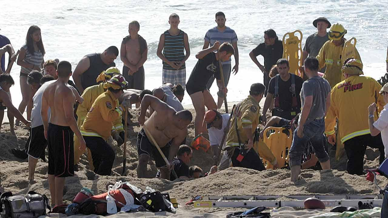 This Monday, July 21, 2014, photo released by the Half Moon Bay Review shows emergency crew workers and volunteers working to rescue a man at Francis State Beach in Half Moon Bay,