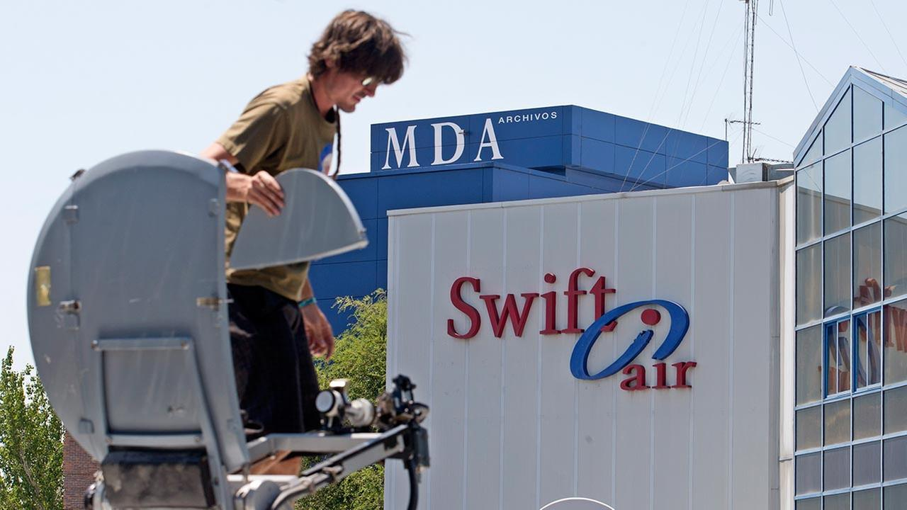 A television camera operator mounts a satellite dish on top of a van outside the Swiftair offices in Madrid, Spain, Thursday, July 24, 2014.