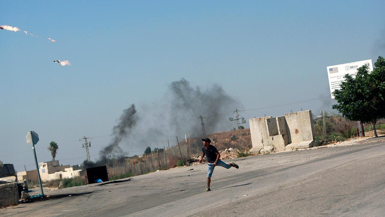 A Palestinian protester throws a Molotov cocktail towards Israeli troops, following a protest against the war in the Gaza Strip