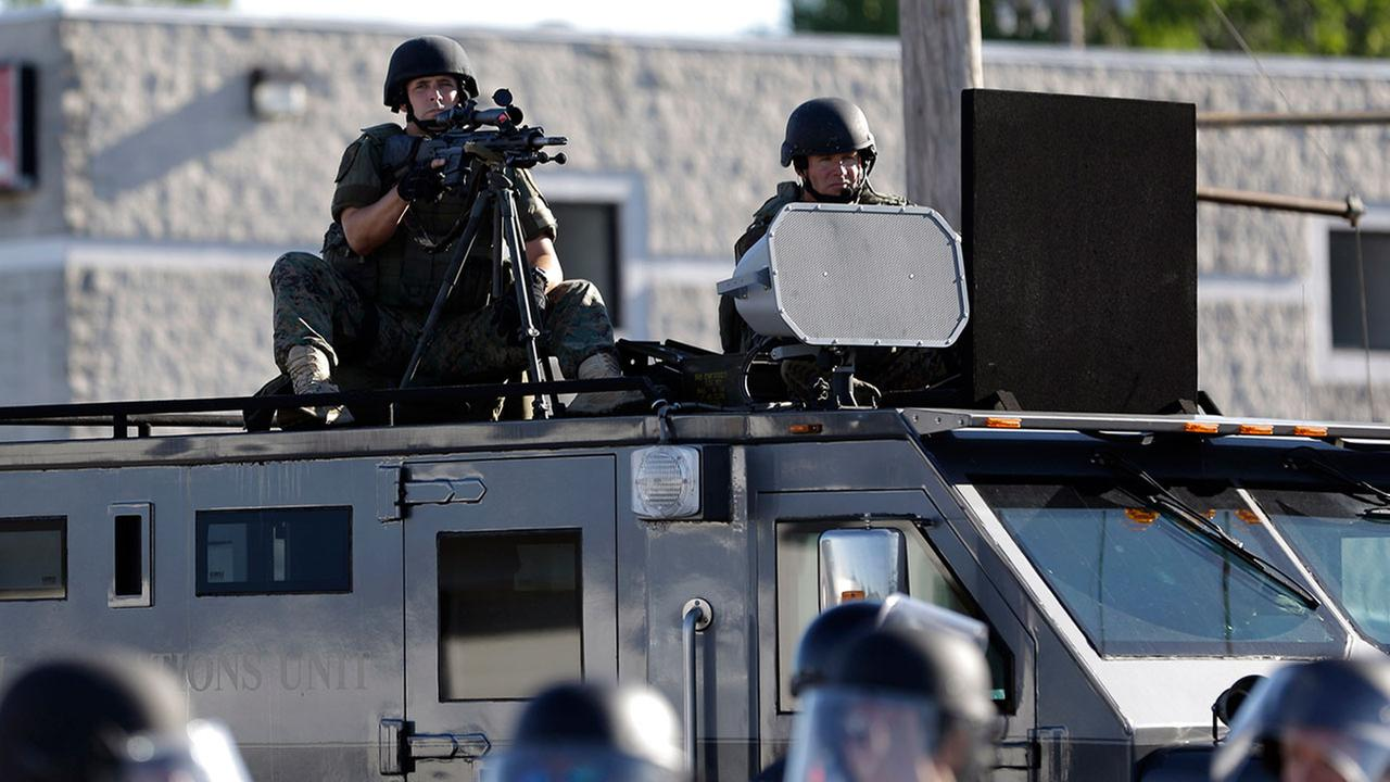 FILE: A police tactical team moves in to disperse a group of protesters following the shooting of a young man by a policeman in Ferguson, Mo.