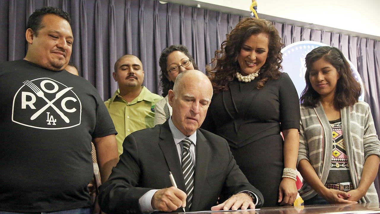 California Gov. Jerry Brown signs a bill mandating the paid leave that supporters say will guarantee that workers dont lose their jobs or their paychecks if they or a family membe