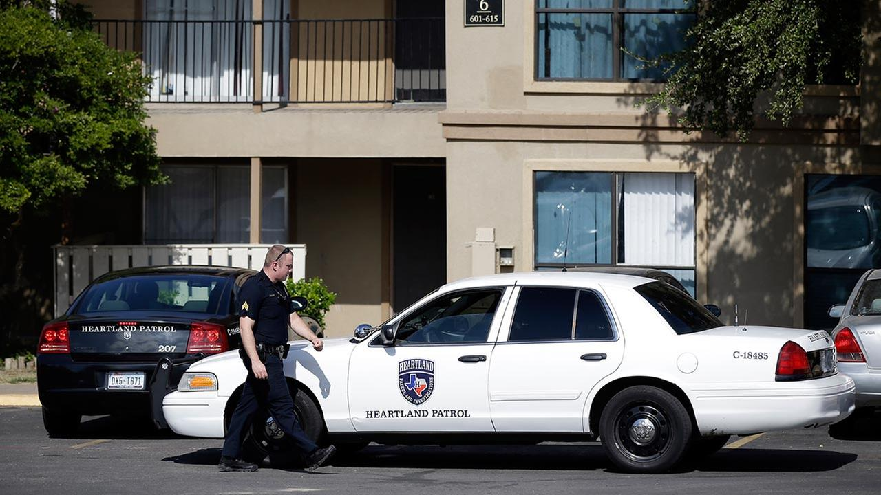 Law enforcement vehicles are parked in front of building six of The Ivy Apartments complex, Wednesday, Oct. 1, 2014, in Dallas.