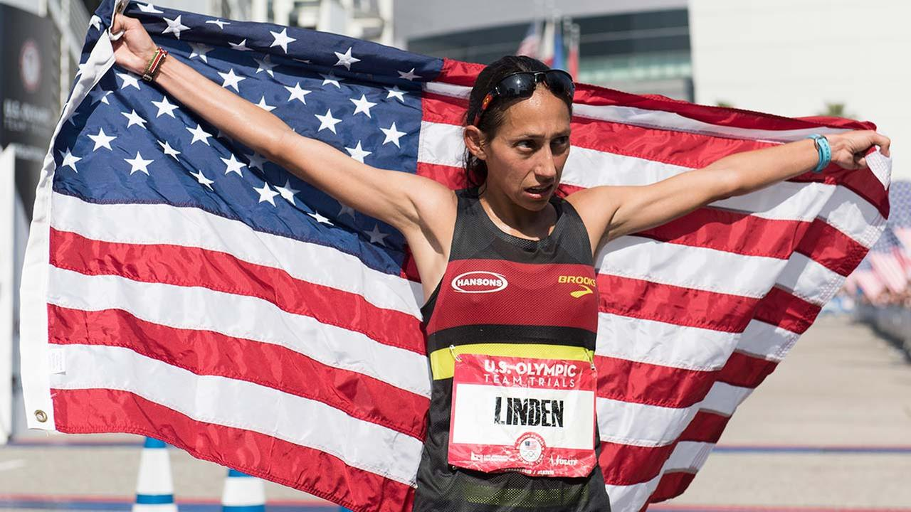 (FILE) Desiree Linden holds up the United States flag at the finish line during the U.S. Olympic marathon trials. (AP Photo/Kelvin Kuo)