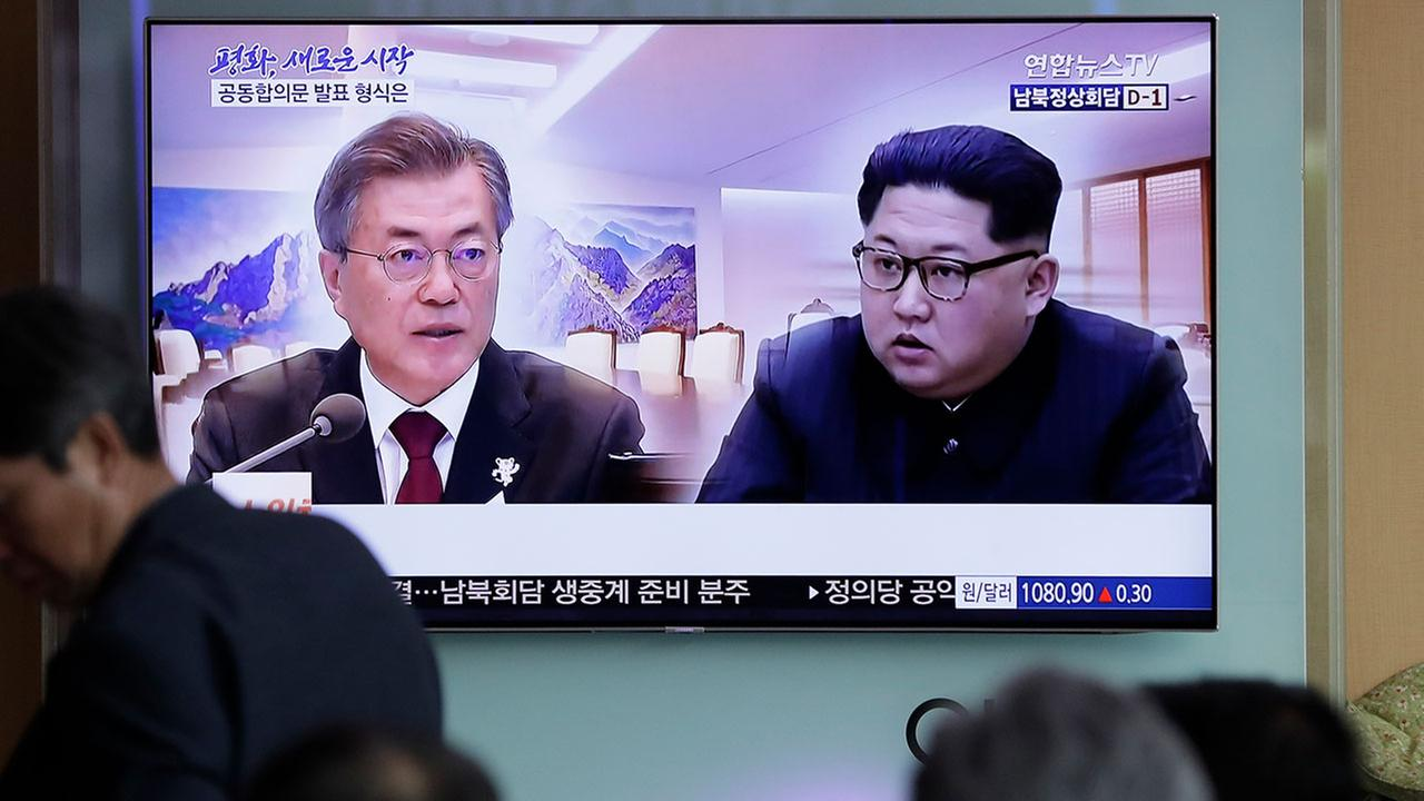 People watch a TV screen showing file footage of South Korean President Moon Jae-in and North Korean leader Kim Jong Un during a news program ahead of the inter-Korean summit.