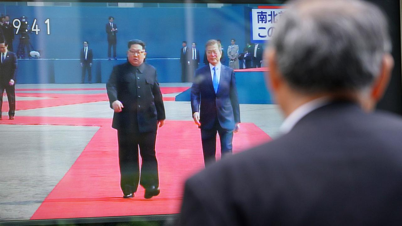 A man in Tokyo watches a TV screen showing live news footage of North Korean leader Kim Jong Un and South Korean President Moon Jae-in walking together Friday, April 27, 2018.