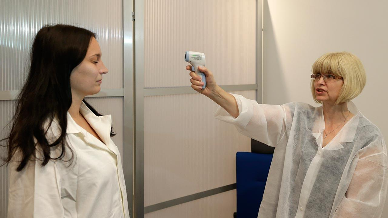 Medical staff demonstrates how to take the temperature of a passenger at the Vaclav Havel Airport in Prague, Czech Republic