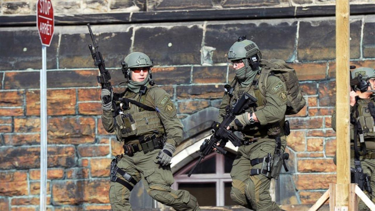 A Royal Canadian Mounted Police intervention team responds to a reported shooting at Parliament building in Ottawa, Wednesday, Oct. 22, 2014.