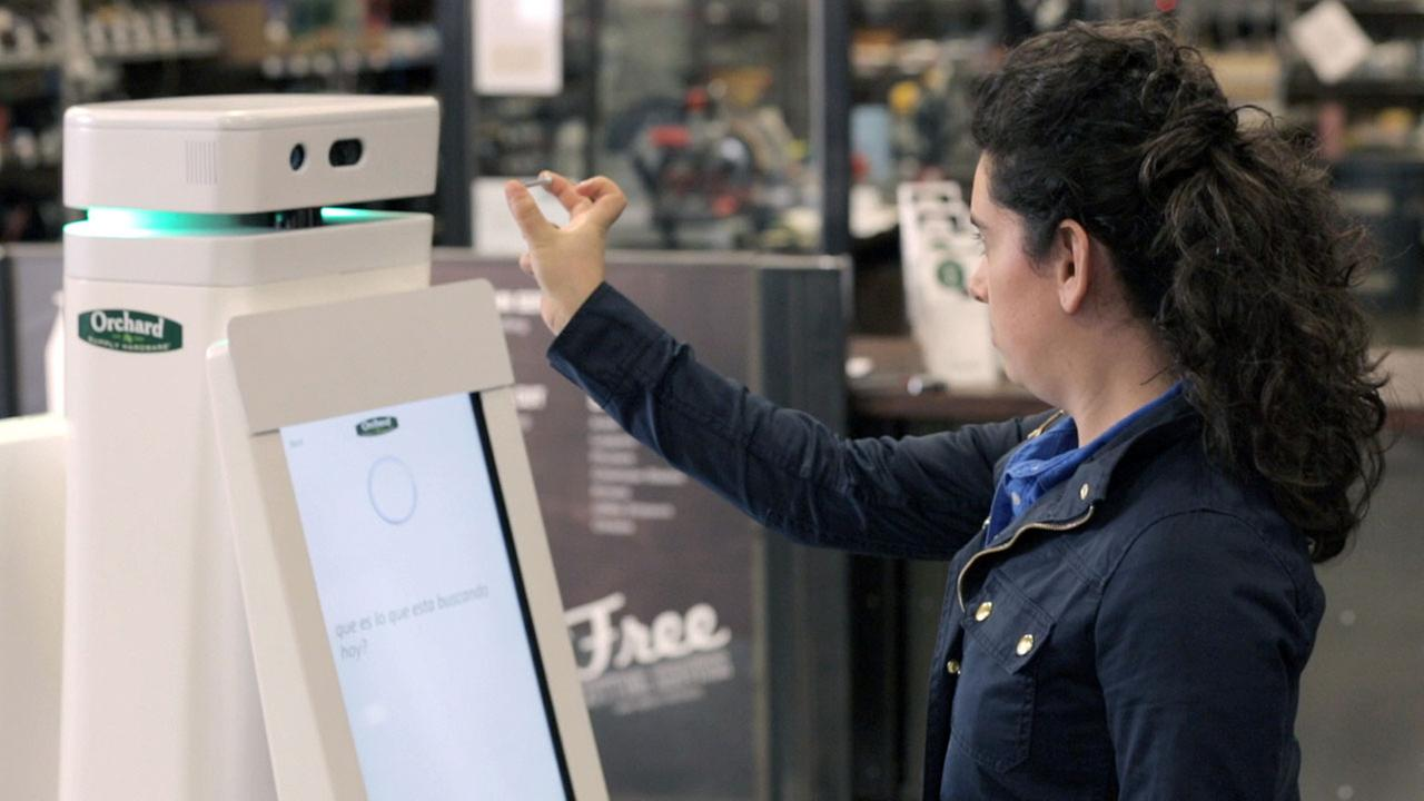 In this undated image provided by Lowes, a woman holds a nail up to be scanned by an OSHbot robot.