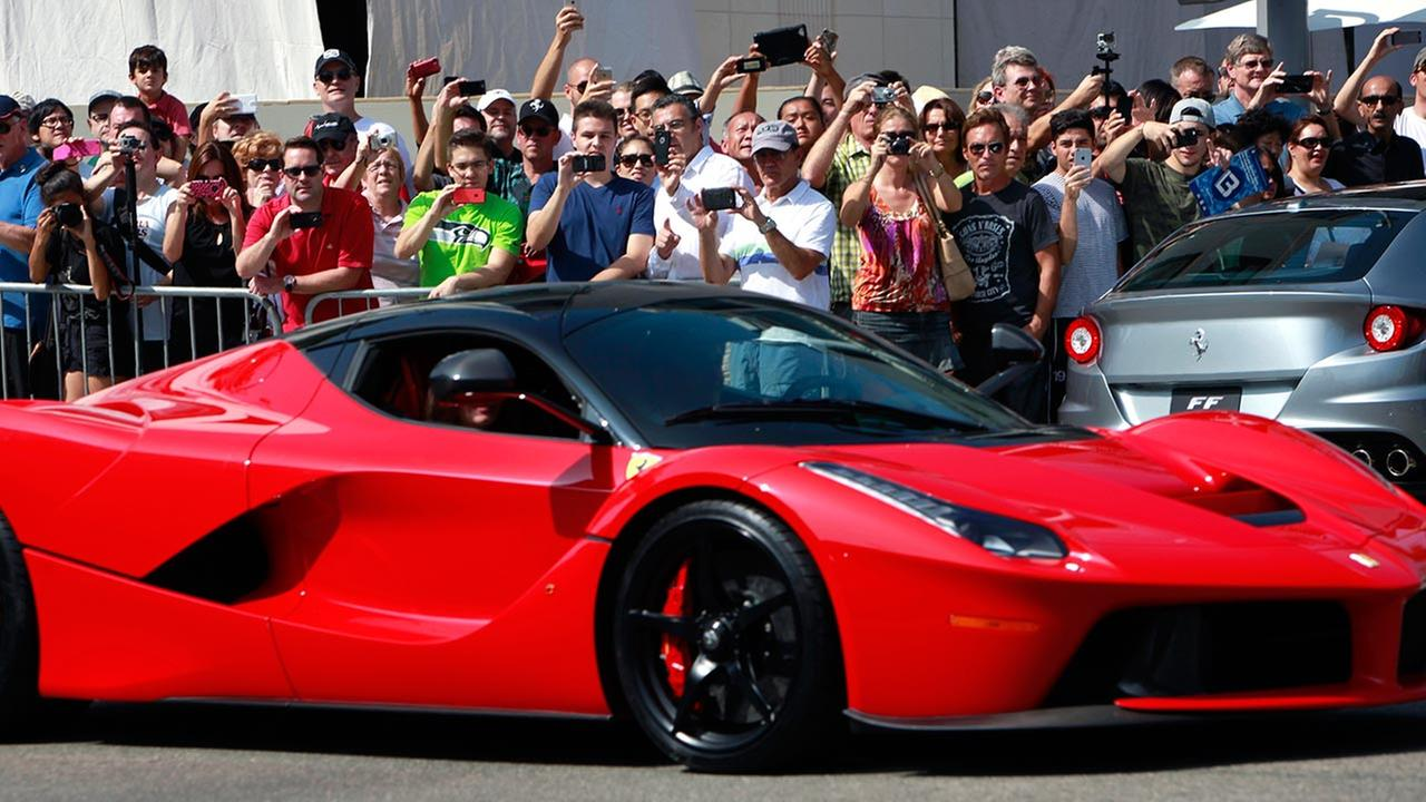 Ferrari enthusiasts take photos of a Ferrari driving by Rodeo Drive in Beverly Hills, Calif. on Sunday, Oct. 12, 2014.