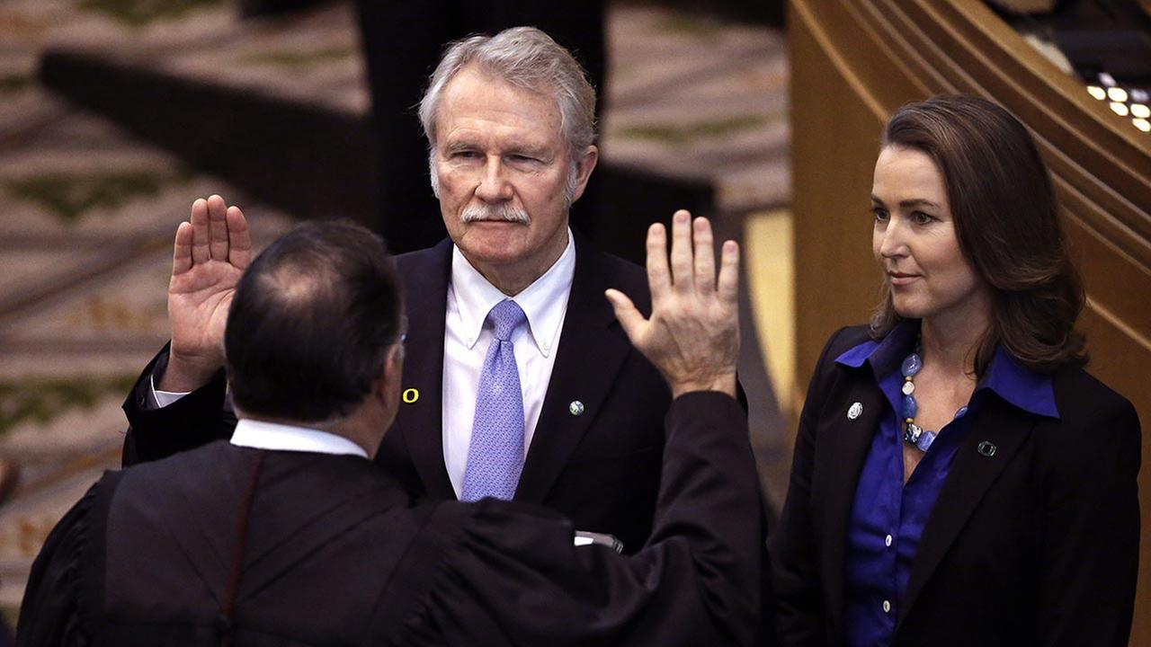 In this Jan. 12, 2015 file photo, Oregon Gov. John Kitzhaber, middle, is joined by his fiancee, Cylvia Hayes, as he is sworn in for an unprecedented fourth term